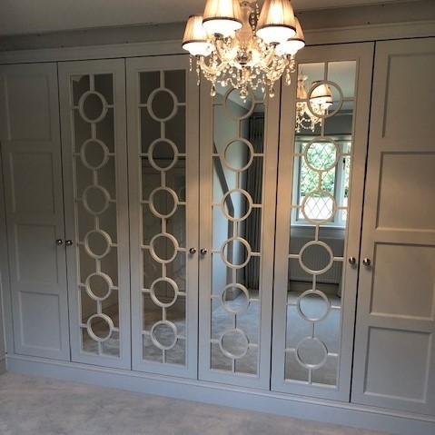 Pop wardrobe doors, panelled and mirrors. Lampshade. Cream colour, bedroom.